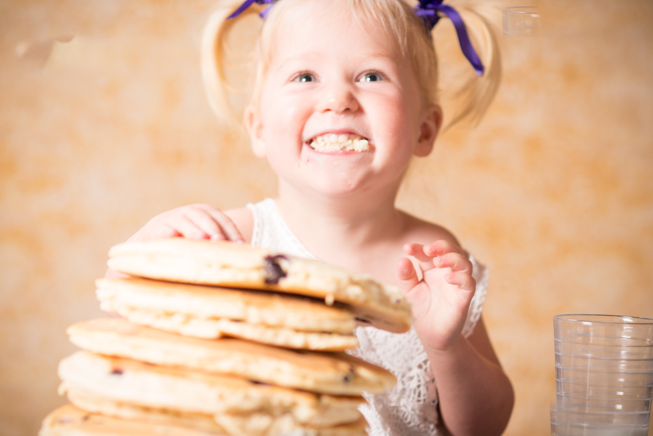 Little girl smiling because she has a huge pile of pancakes