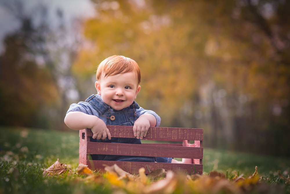 Red haired boy in overalls and a milk crate