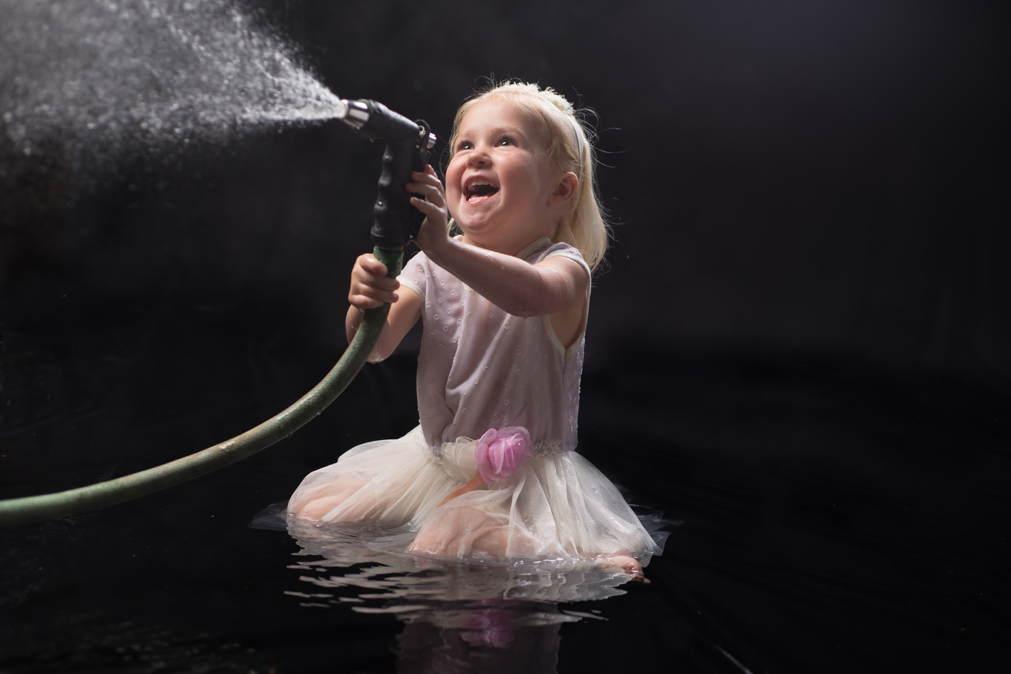 Laughing child spraying a hose