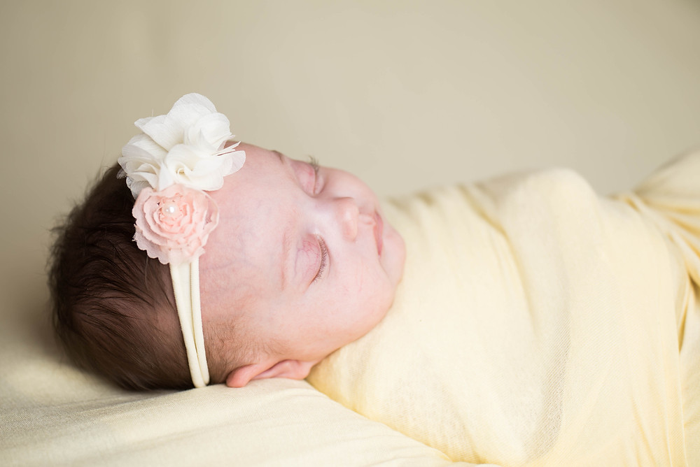 Newborn Baby Girl swaddled up in all yellow