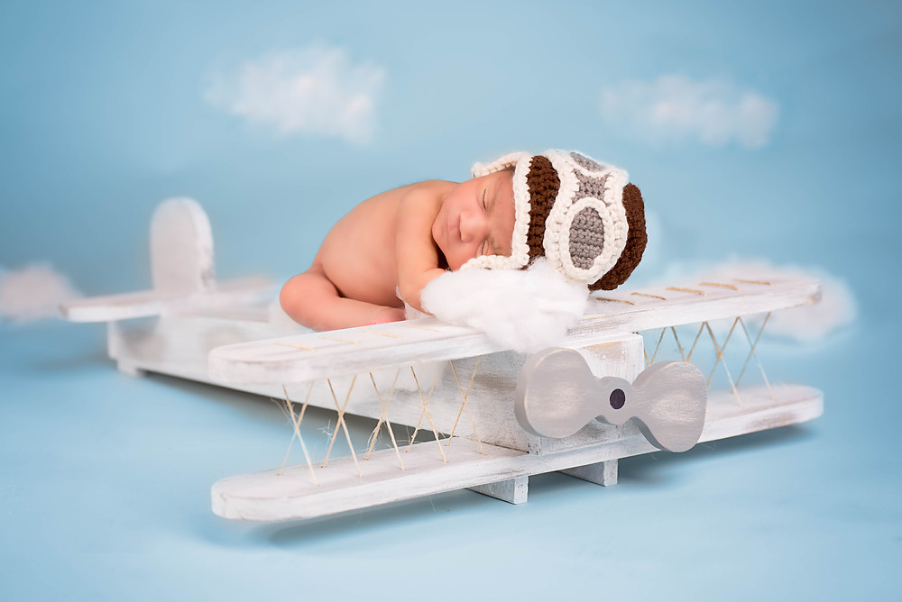 Baby aviator on a wood airplane photography prop in Overland Park studio
