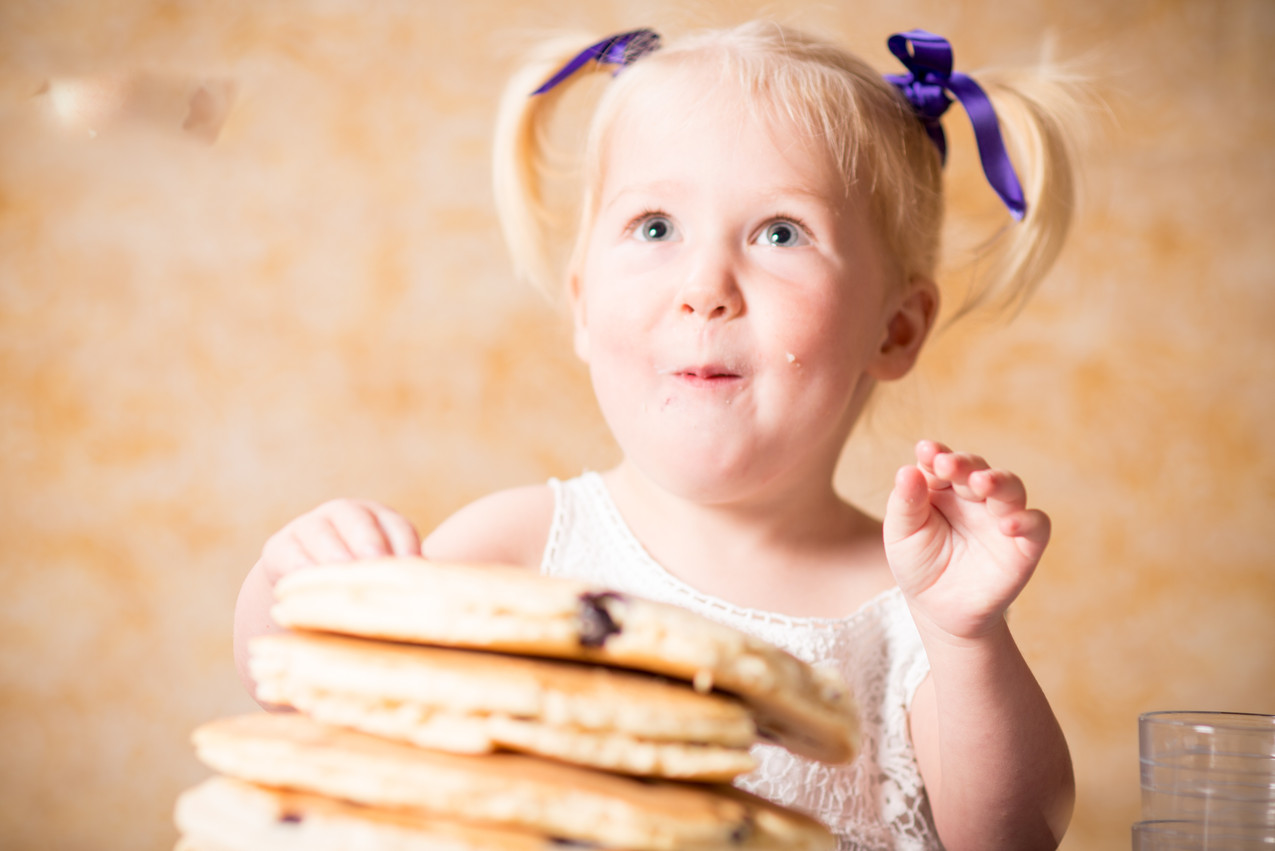 Candid photography of child eating pancakes