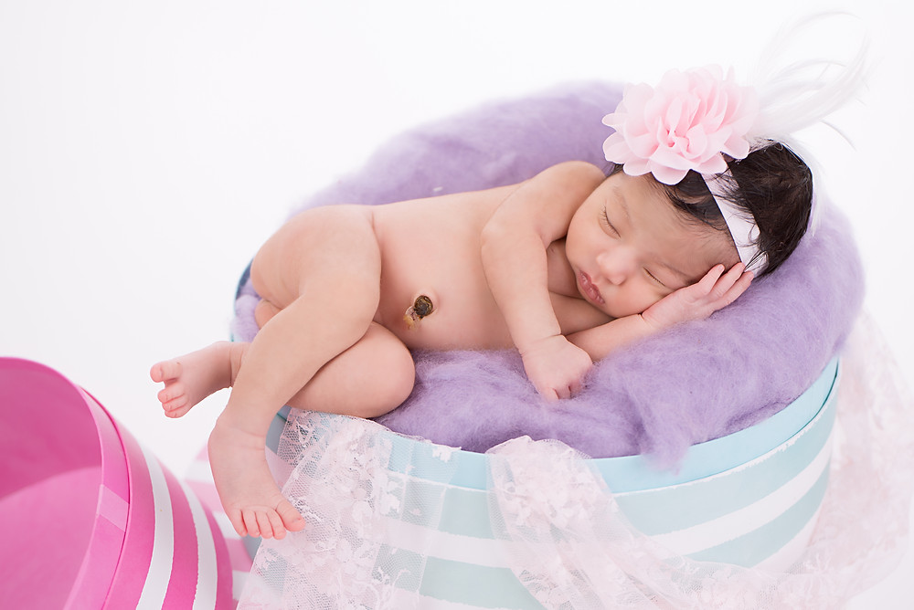 Beautiful newborn girl with long black hair in best Overland Park newborn photography studio