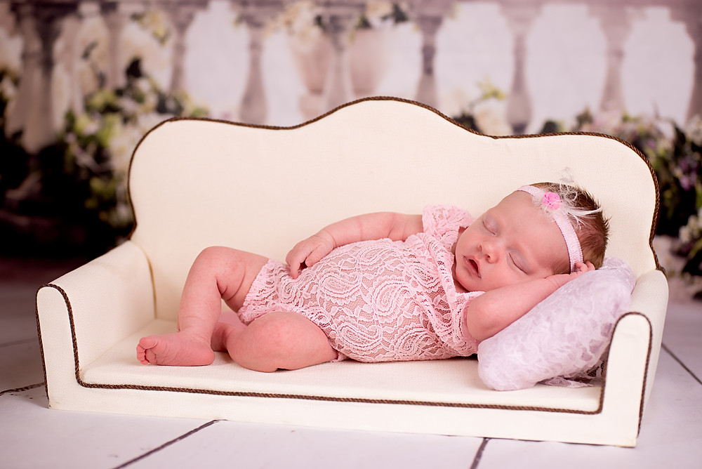 Baby girl relaxing on the touch in lace romper