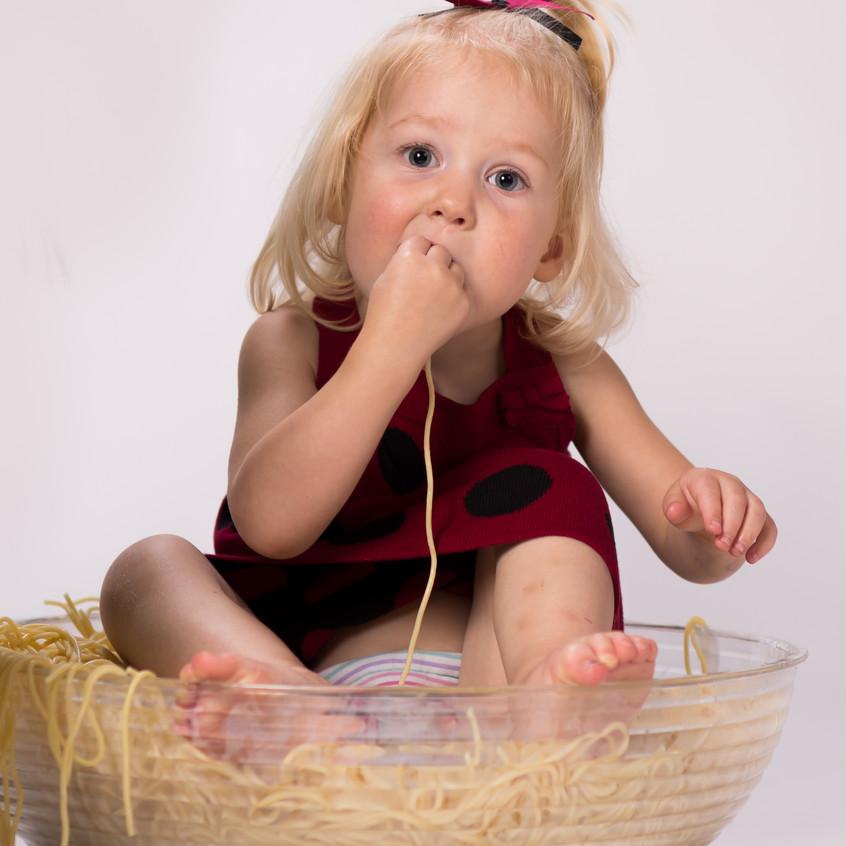 Child eating spaghetti at Olathe photographer