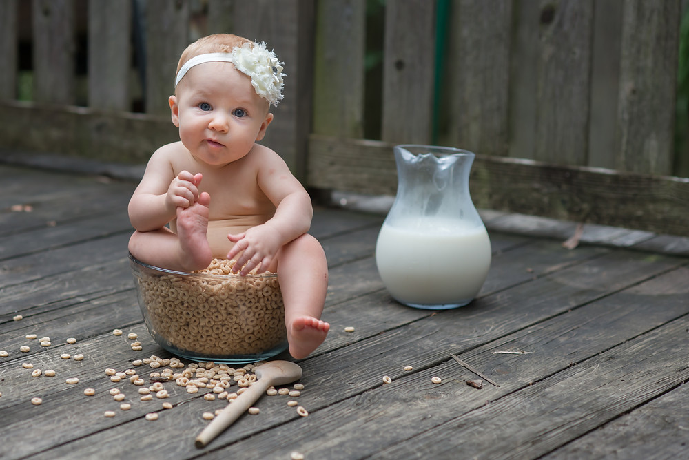 6 month baby in a bowl of cheerios