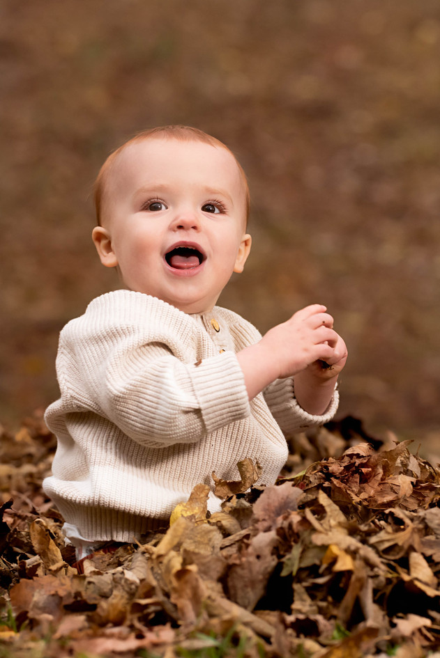 Baby in a pile of leaves