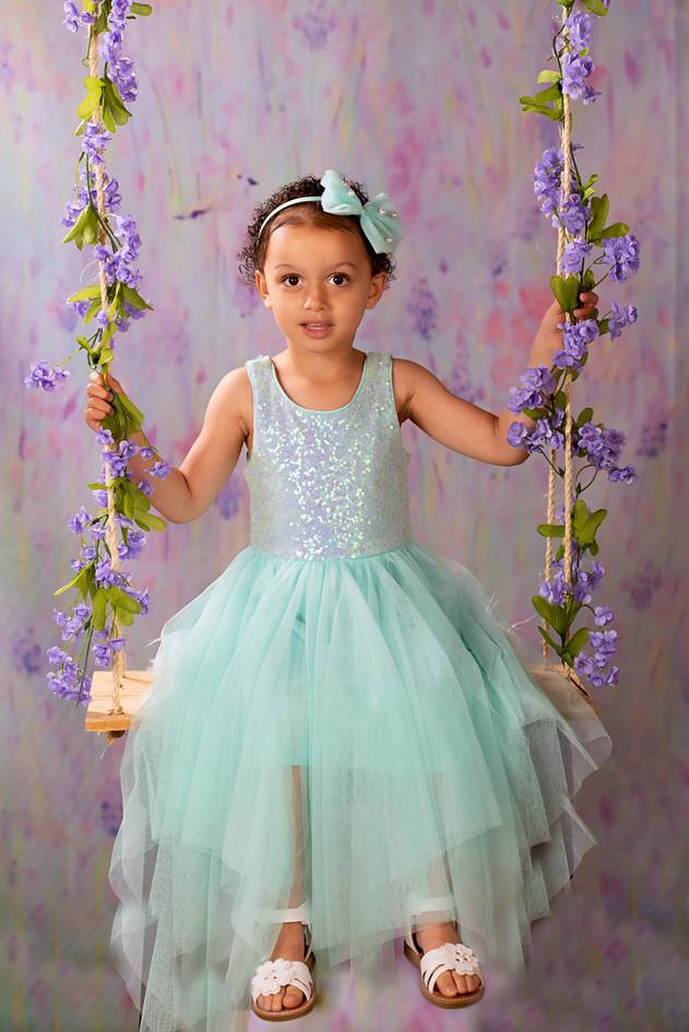 Little girl on a flower covered swing