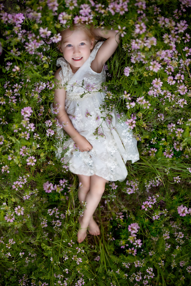 Ariel view of a little girl laying in a patch of flowers