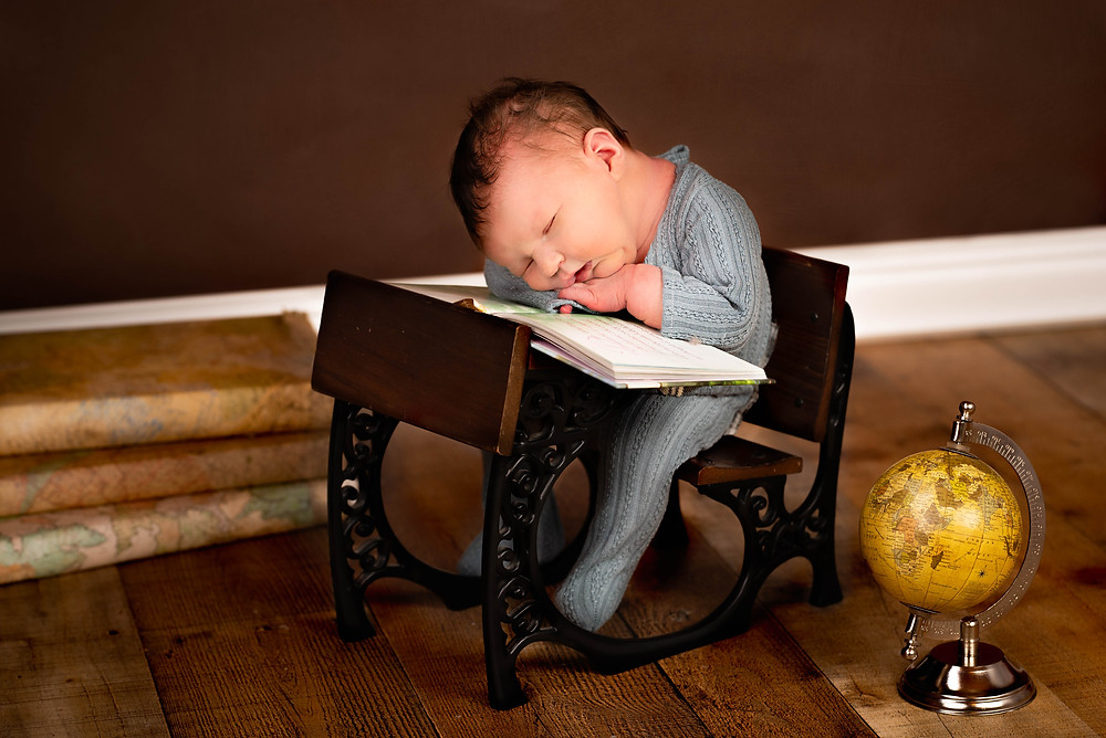 Newborn baby sitting at a tiny desk reading a book by Overland Park's best newborn photographer