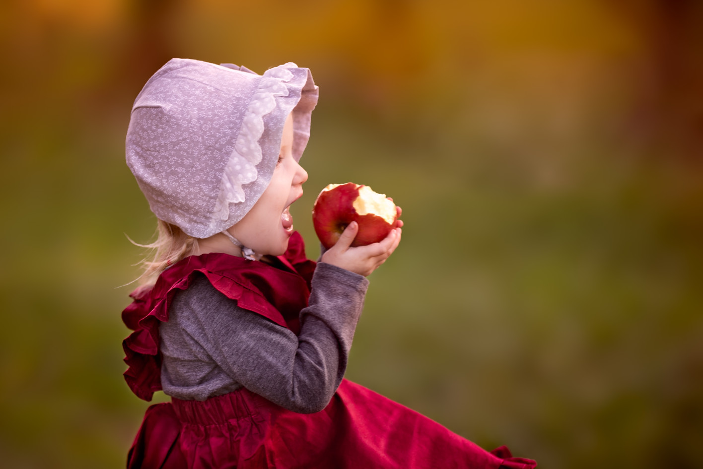Old fashioned toddler eating an apple portrait