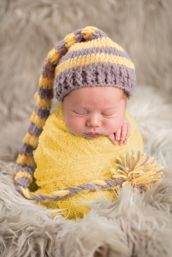 Baby boy wrapped in yellow with grey and yellow sleepy cap in Overland Park photography studio