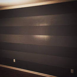 A interior painted wall with seven horizontal columns of different paint colors and paint sheens. A uniquely interior painted wall.