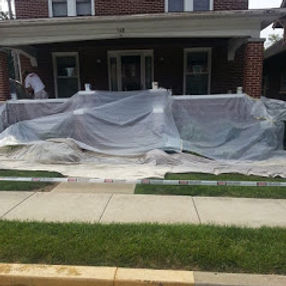 The exterior front of a house that is being prepared for exterior painting. There is plastic and canvas tarps covering the porch floor and front yard.