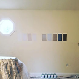 This interior wall has many small square paint samples on it in a variety of colors. A interior painting project.