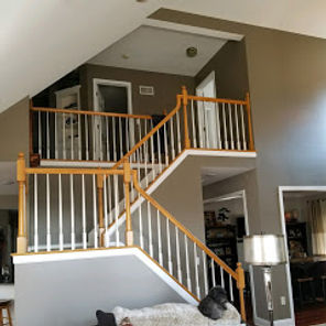 The interior of a home that has grey walls and a set of stairs with handrails and spindles. A interior painting project.