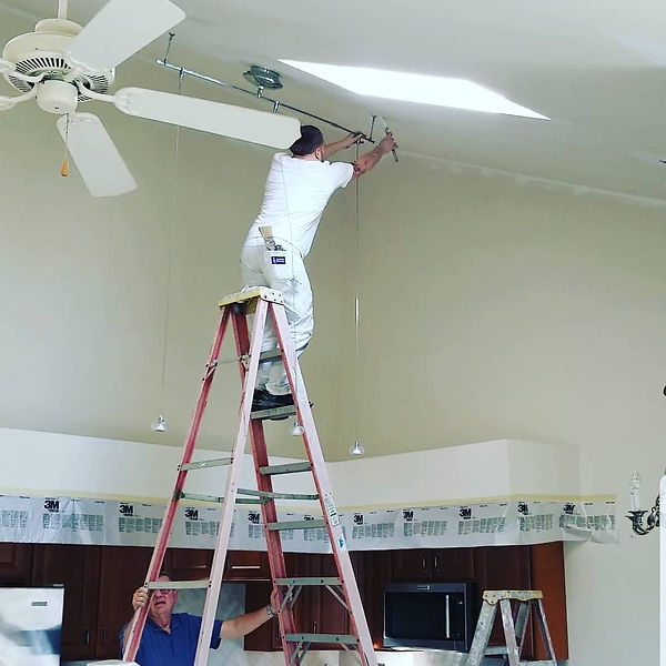 Painter standing on a ladder in the interior of a townhouse painting a ceiling. There is a homeowner holding the bottom of the ladder. Interior painting project done by Benji's Painting in Ephrata PA.