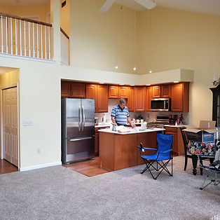A man standing in a open concept kitchen with yellow painted walls behind him. Interior painting.