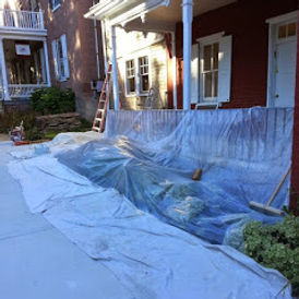 The side exterior of a building which is being prepered for exterior painting, the floor and sidewalk are covered with plastic sheeting and canvas tarps.