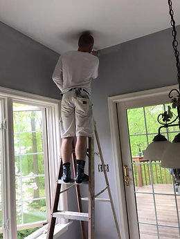 The owner of Benji's Painting standing on a ladder inside a house painting interior walls.