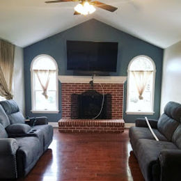 A living room that has a blue painted accent wall and vaulted ceilings. An interior living room painting project.