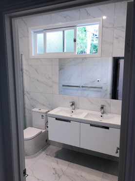 white marbled bathroom with dual sinks a