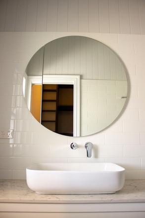 bathroom sink with round mirror