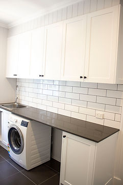 laundry room with black benchtop and whi