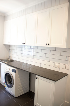 laundry room with black benchtop and white subway tiles