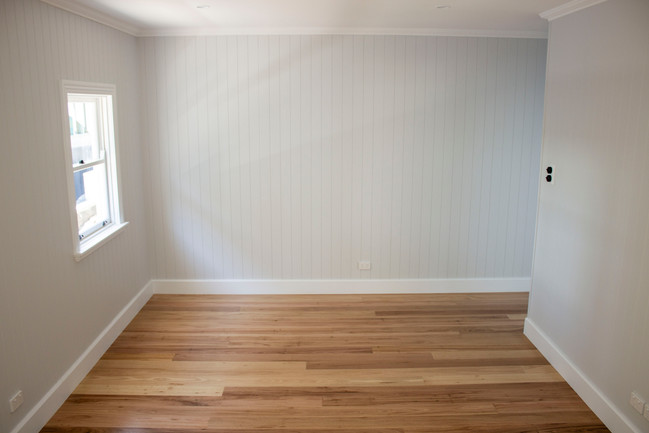 timber flooring of room with white walls