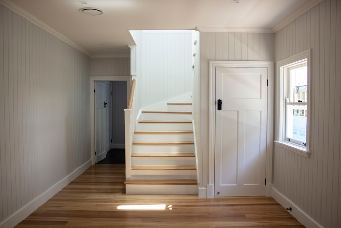 downstairs area with timber flooring and white walls