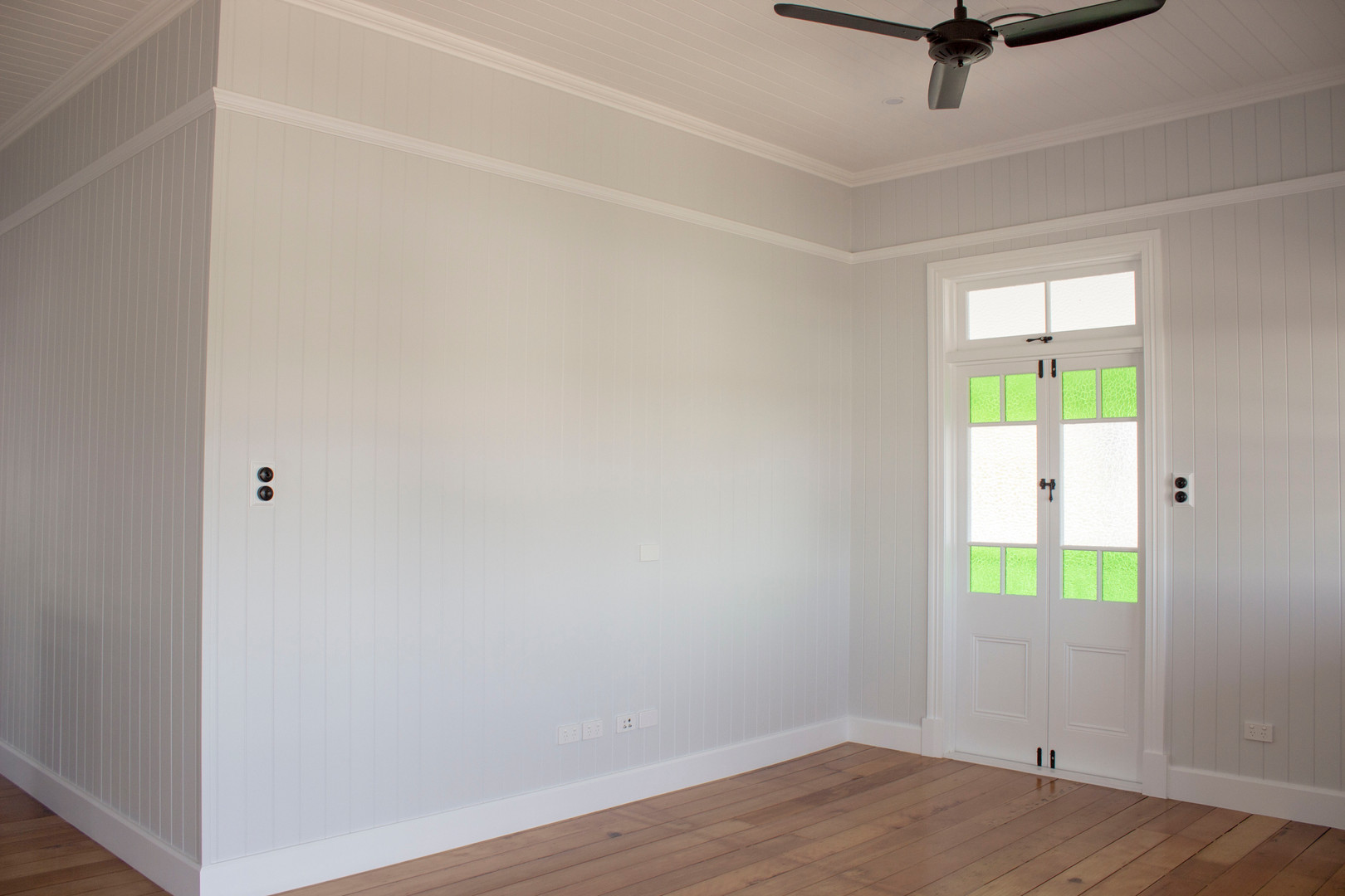 white room with timber flooring and gree