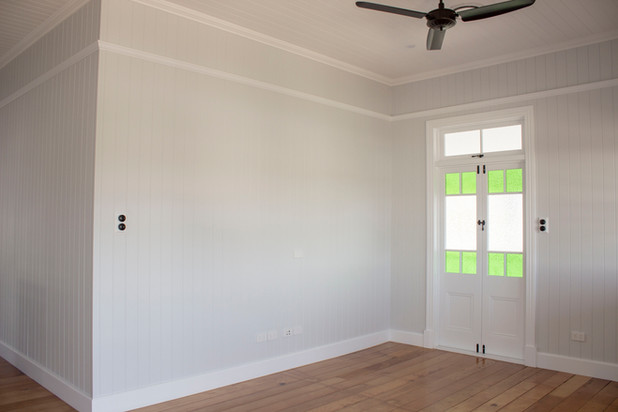 white room with timber flooring and green glass windows