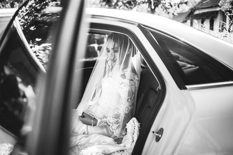 B&W photo of bride sitting in the car