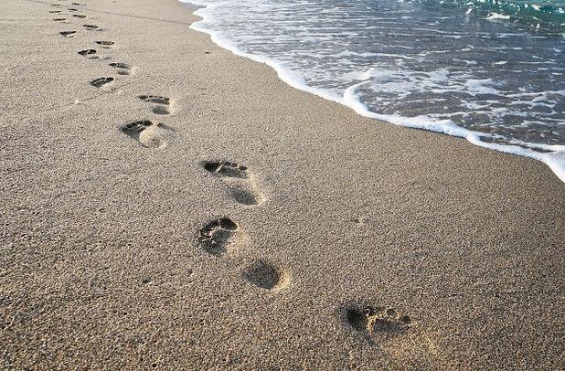 footprints-sand-near-sea-waves_1378-366.