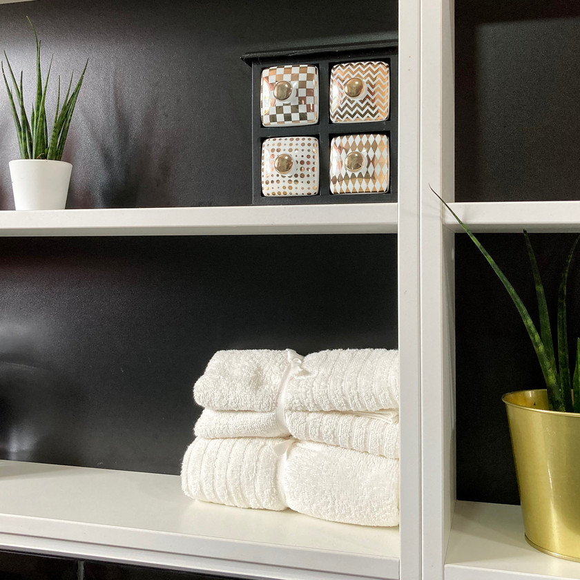 Monochrome shelving with white towels and brass plant pot
