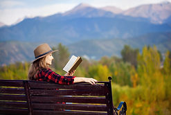 Woman reading in mountains on a bench.jp
