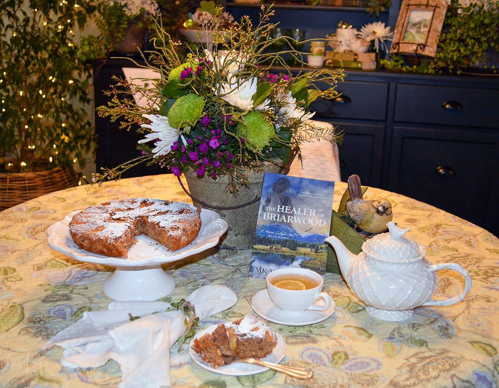 Cast-Iron Irish Apple Cake with tea and The Healer of Briarwood book - MK McClintock