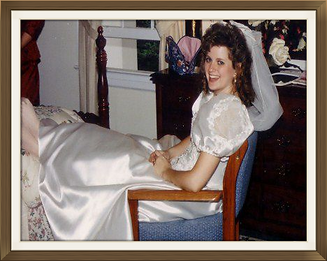 Kelly in wedding dress with feet on bed and looking into camera