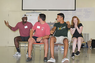 Students laughing in a group of four sitting in chairs while playing an improv game called Taxi