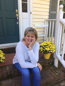 Kelly sitting in a white shirt and jean on the brick steps smiling