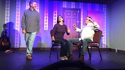 Paul on stage joking with his scene partners.  The background a a light purple