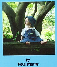 Picture of a baby next to a tree looking to the left in a blue hat and blue dress