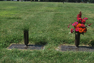Picture of two graves with flowers in one holder and not the other