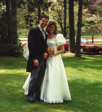Wedding picture of paul in black tux and kelly in white dress outside on green grass