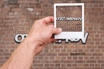 OTC improv logo with hand showing polaroid picture saying OTC improv