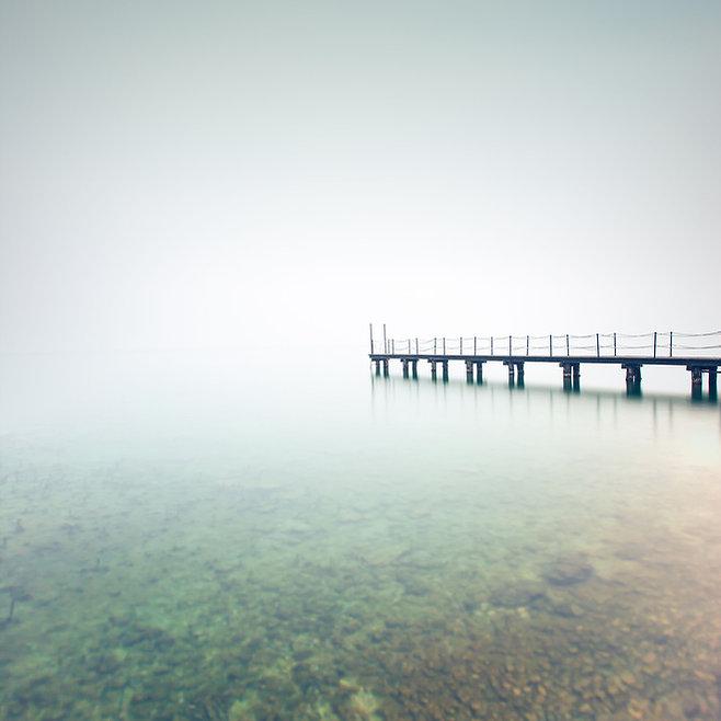 Wooden wharf on foggy lake