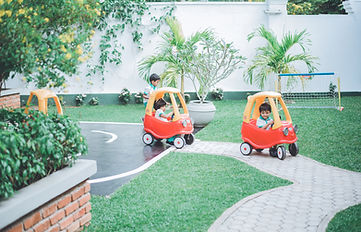 Children riding little cars in the play area in a school in Sri Lanka.