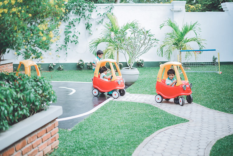 Students riding little cars in a playground at an international school in Sri Lanka.
