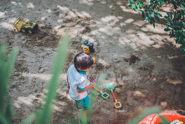 A boy from Jade Drive is playing sand at the sand play area.